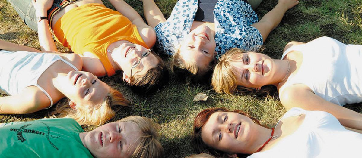 Jugendliche liegen im Rücken im Gras
